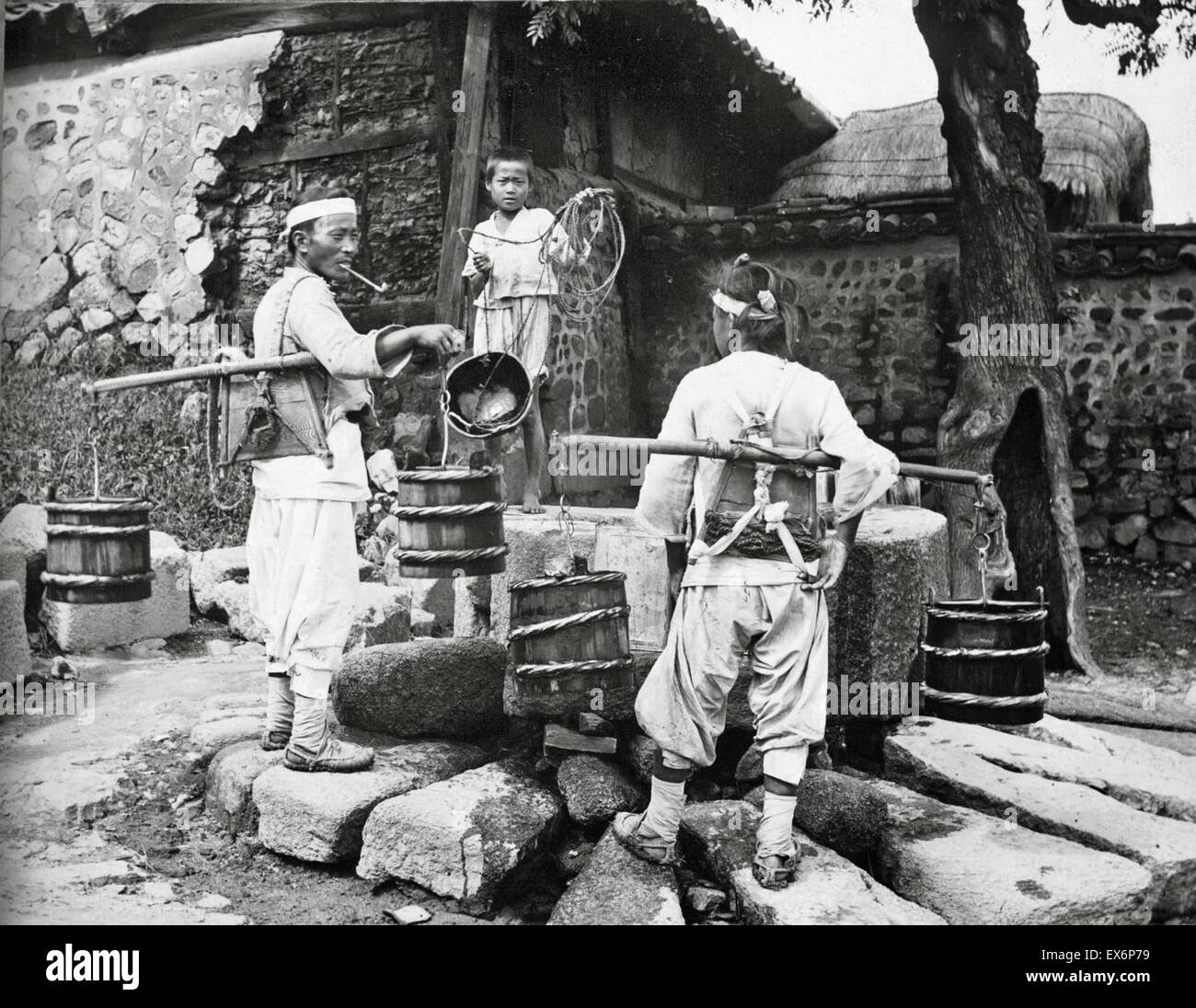 Water carrier visits a village, Korea 1904 - Stock Image