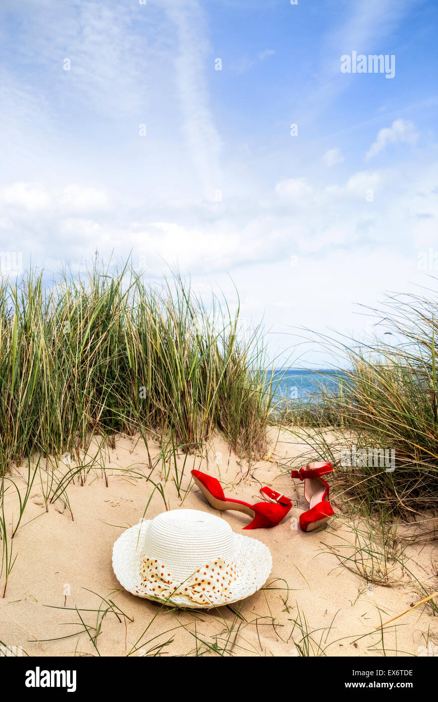 a hat and red shoes are lying in the dunes in the sand - Stock Image