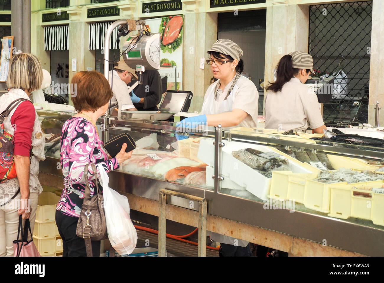 Two ladies shopping at fresh fish market inside Mercato Albinelli, Modena. - Stock Image