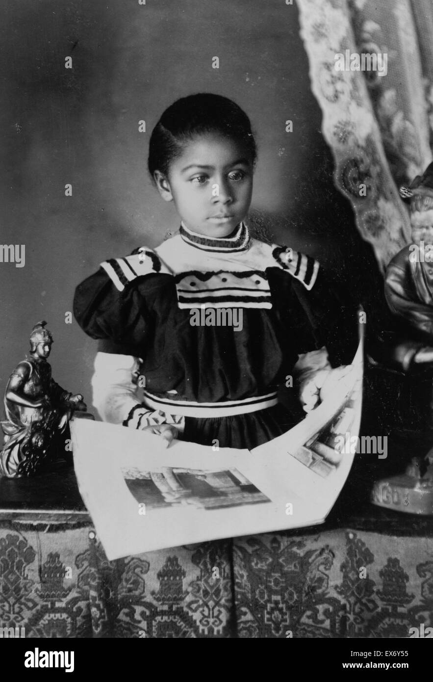 African American girl, half-length portrait, standing at table with illustrated book, facing slightly right. Types - Stock Image