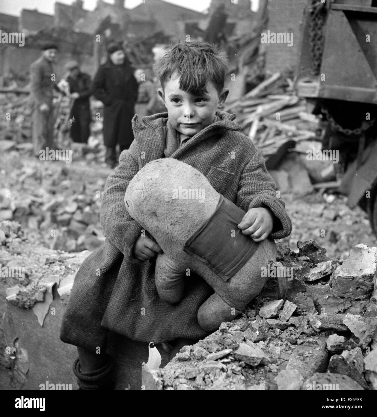 Abandoned boy holding a stuffed toy animal amid ruins following German aerial bombing of London during the Blitz - Stock Image