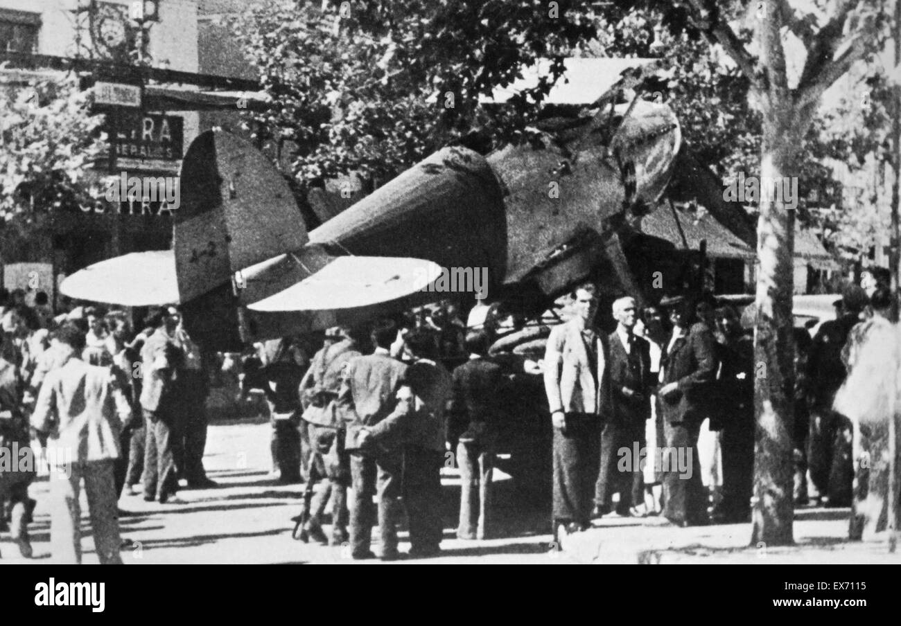 A Nationalist (Fascist) Hawker Fury aircraft lands in a main street in the Spanish city of Badajoz, Crowds of civilians - Stock Image