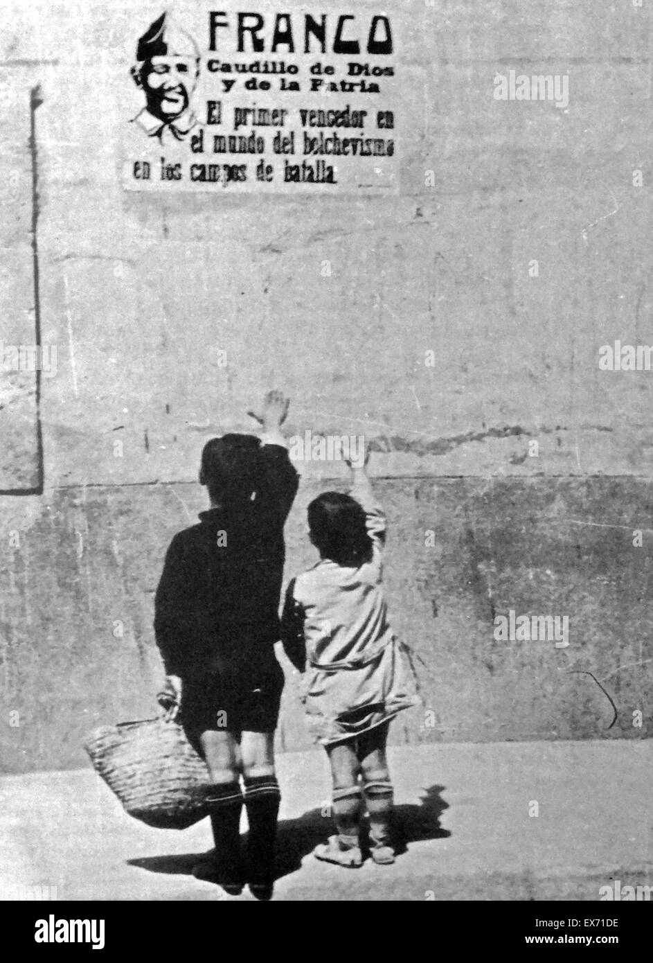 Children salute General Franco on a wall poster in Spain, during the Spanish Civil War. 1937 - Stock Image