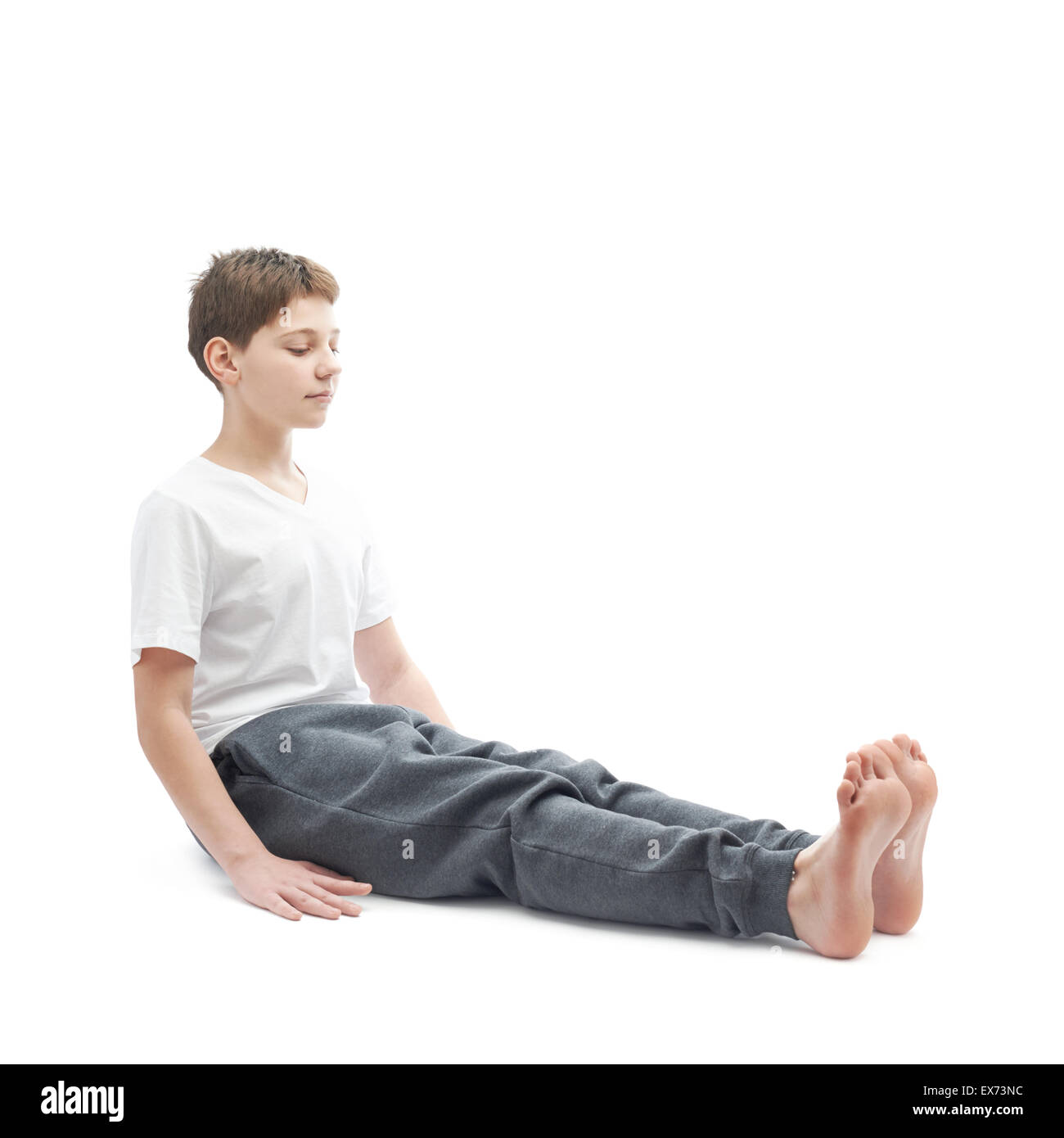 Young boy stretching or doing yoga - Stock Image