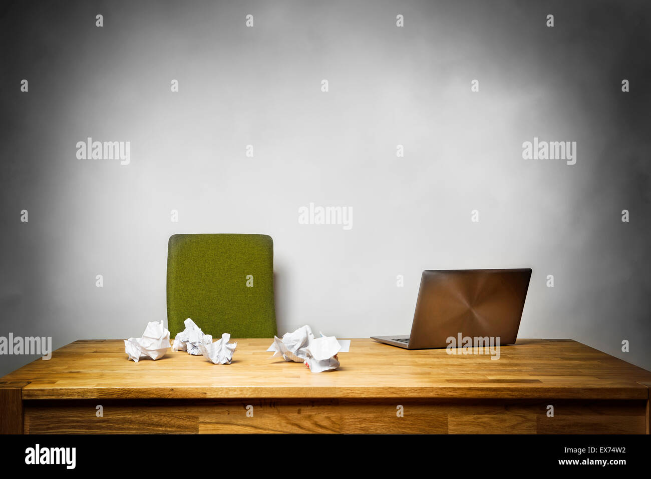 Image of an empty office with chair, laptop and crumpled papers on the desk - Stock Image