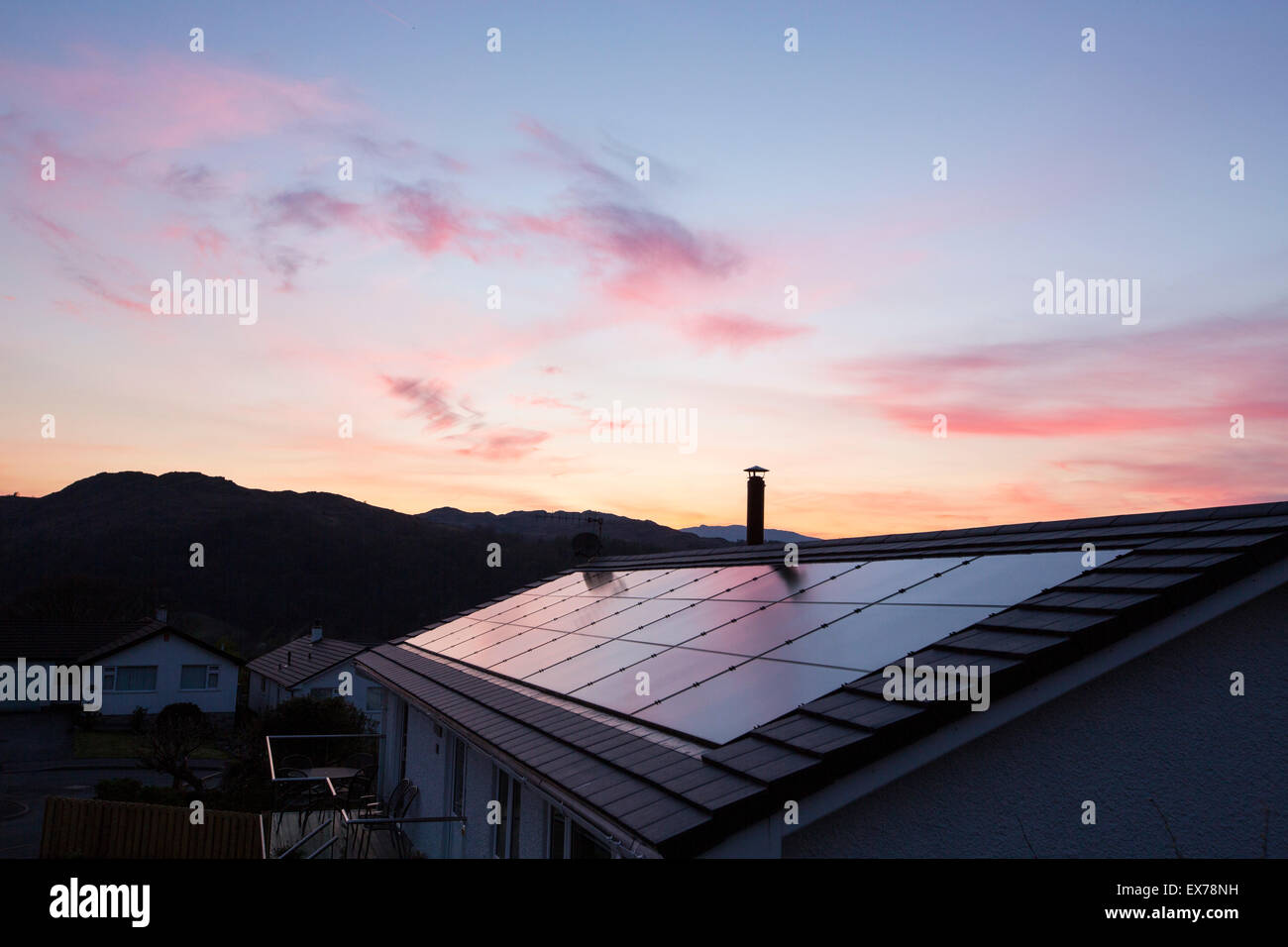 Built in solar panels on a house roof in Ambleside, Lake District, UK, at sunset. - Stock Image