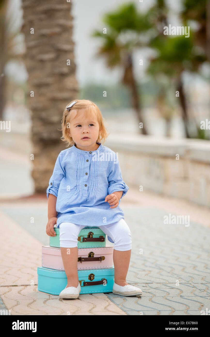 Little girl sitting on a stack of suitcases - Stock Image