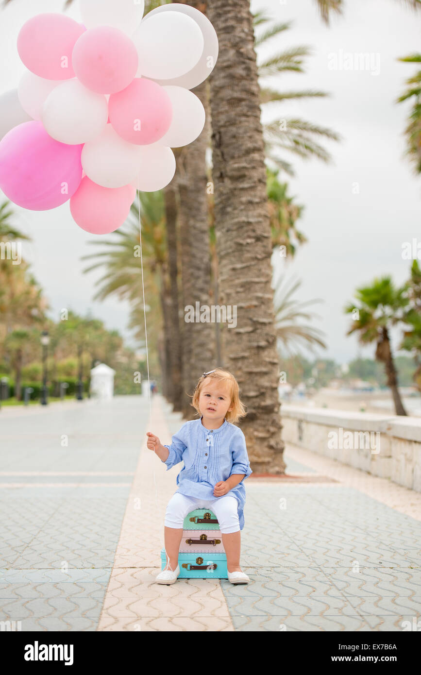 Happy little girl holding a bunch of balloons - Stock Image