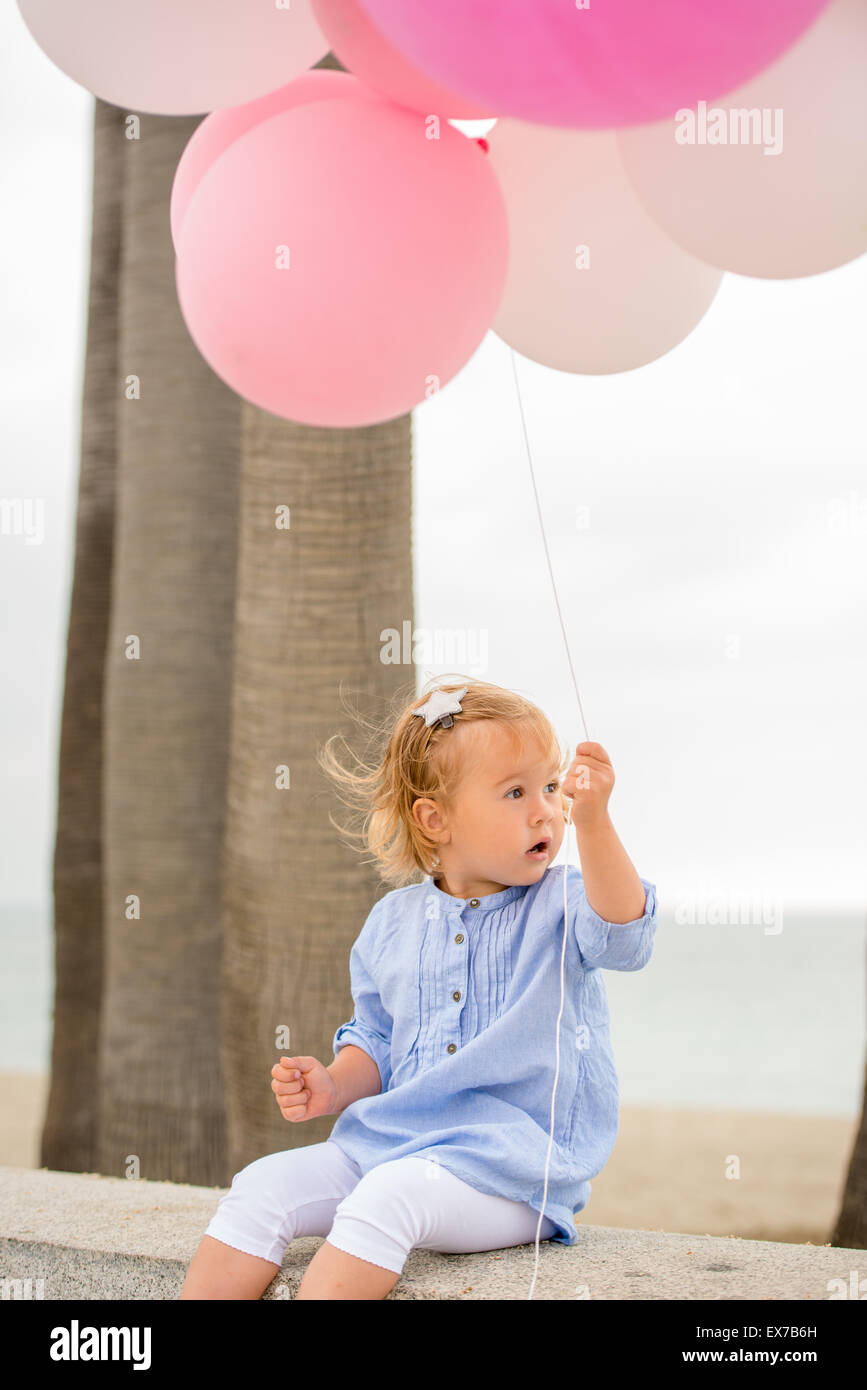 Cute little blond girl holding party balloons - Stock Image