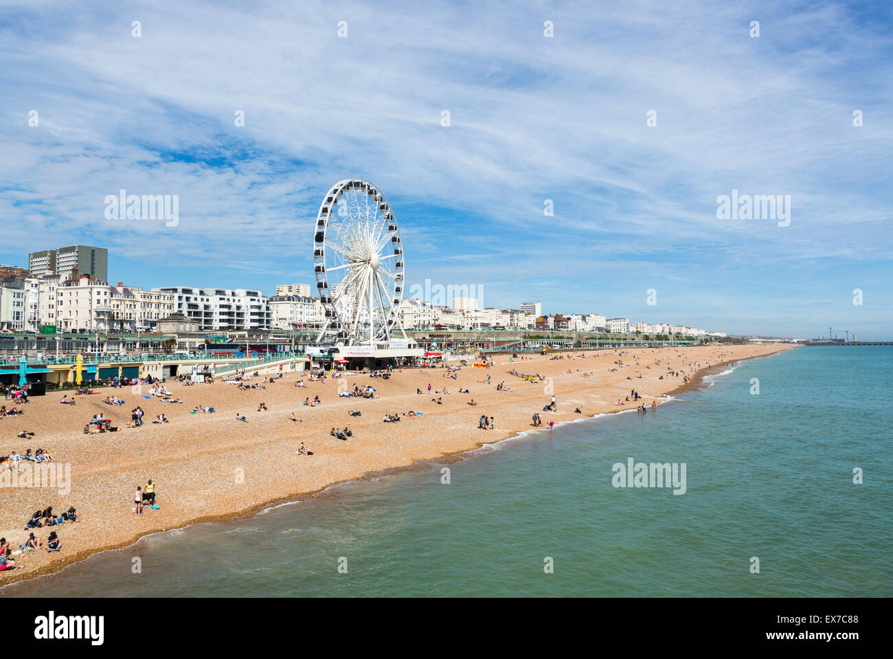 Brighton Beach with seafront promenade and Brighton Wheel on a sunny summer's day, Brighton, East Sussex, UK - Stock Image