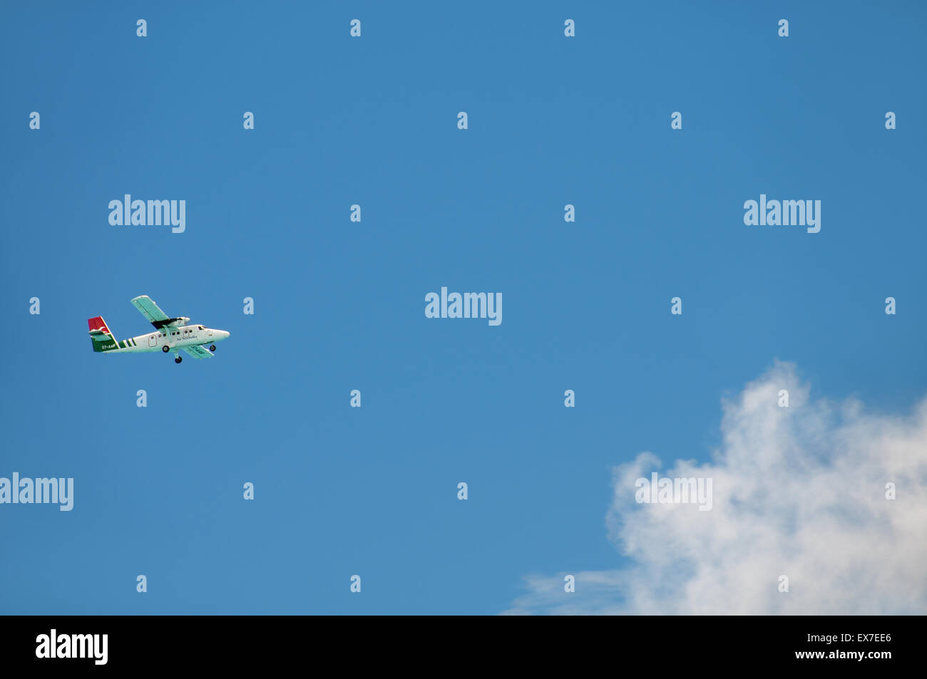 A small passenger plane flies over a cloud, Denis island, Seychelles - Stock Image