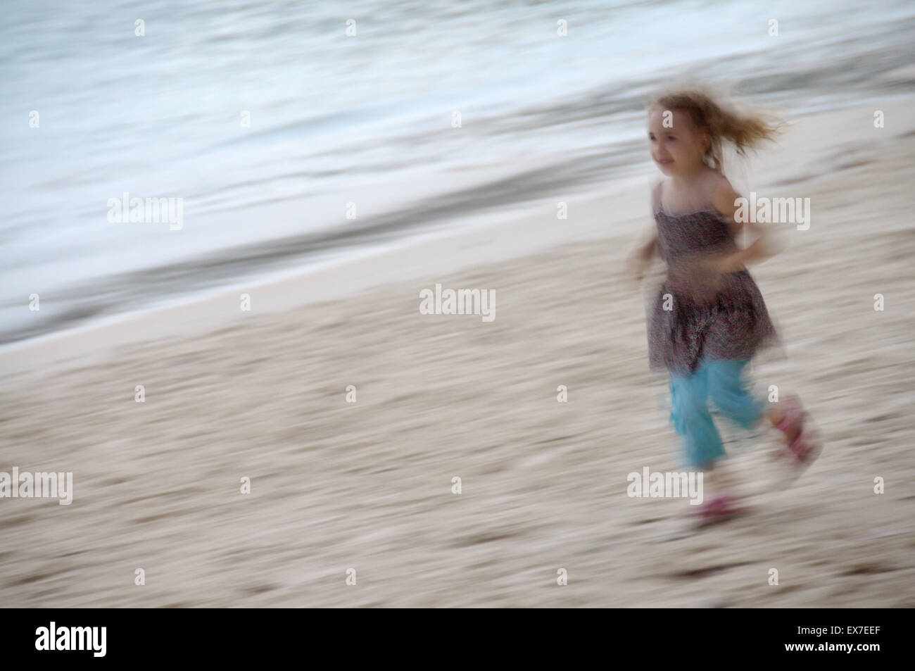 Little girl in a sundress running along the sandy shores of the Indian Ocean, Mahe island, Seychelles - Stock Image
