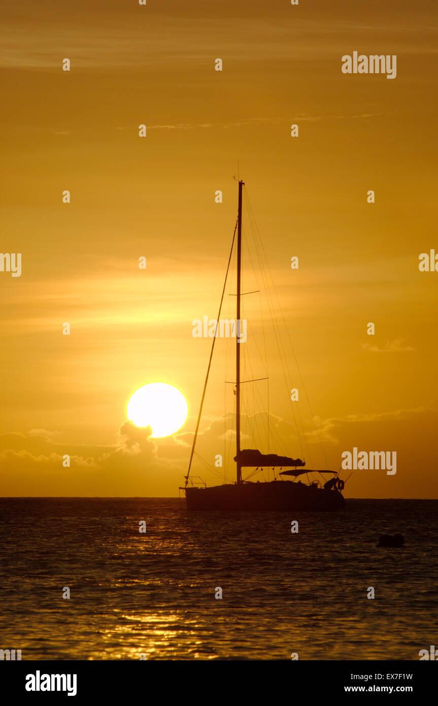 Sailing yacht at sunset, Mahe island, Indian Ocean, Seychelles - Stock Image