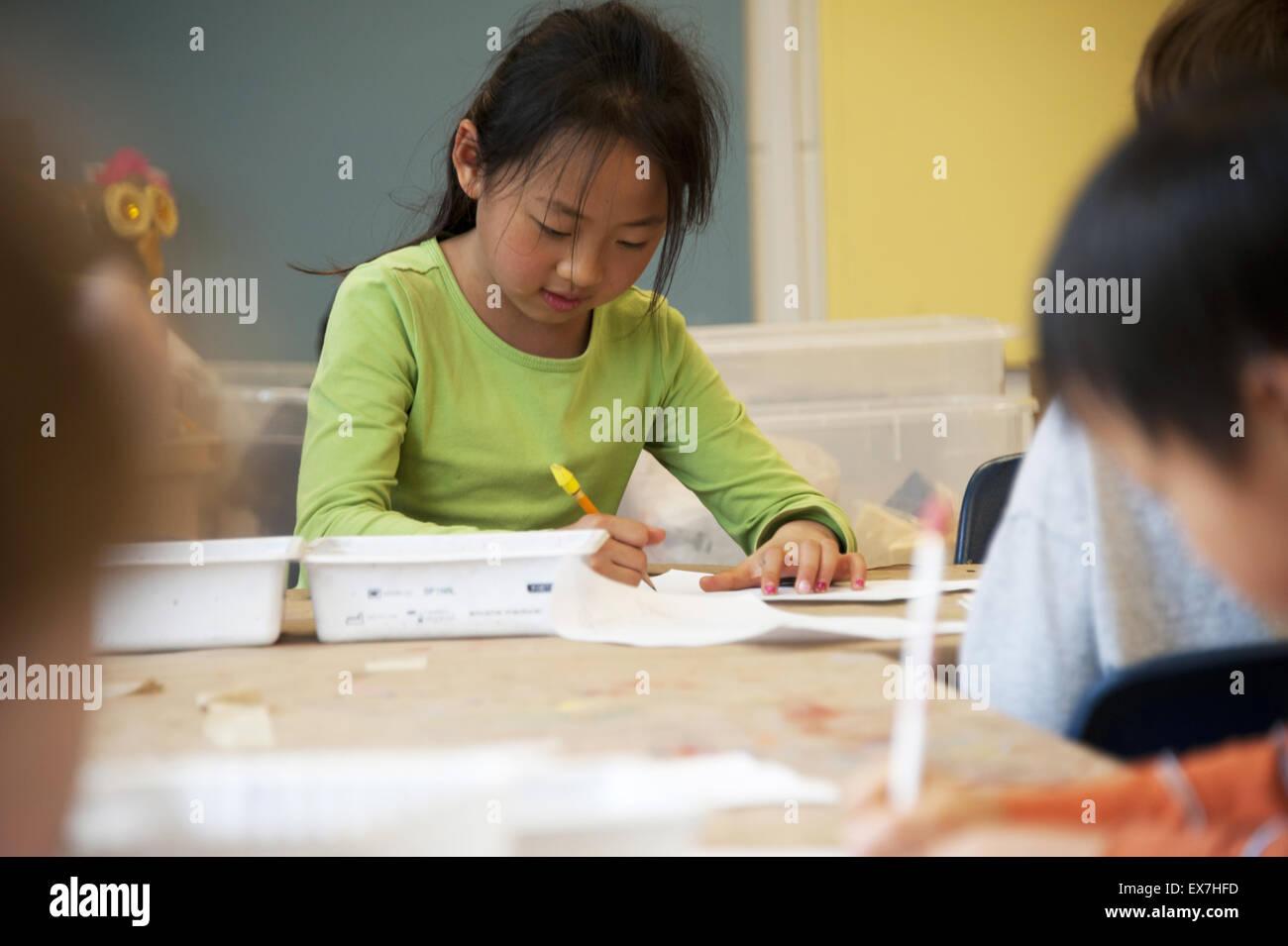Asian minority student working in a school classroom in metropolitan, Atlanta, Georgia. - Stock Image