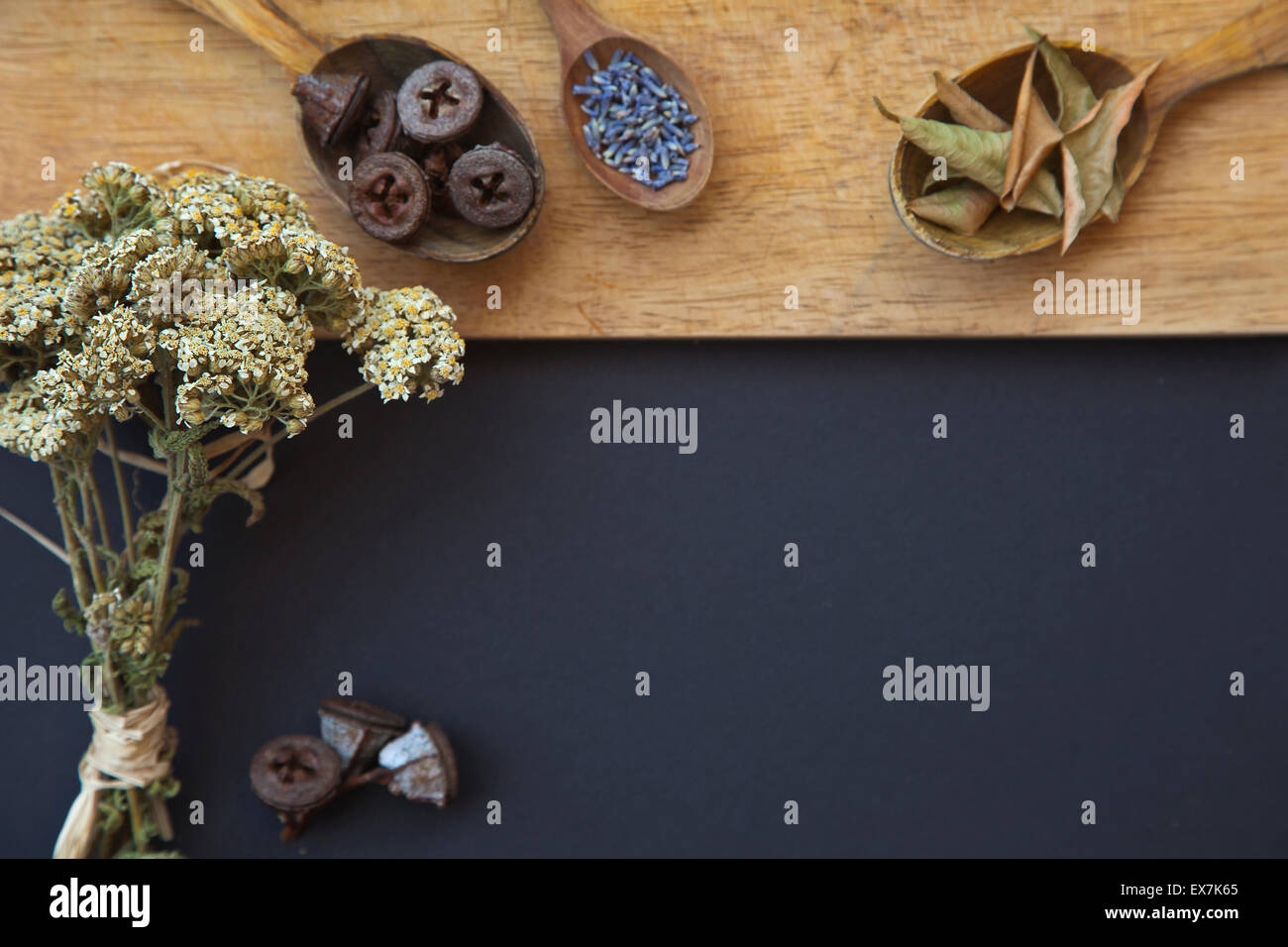 Kitchen background with copy space, Old Wooden cutting board and dark black table surface. Restaurant menu background - Stock Image