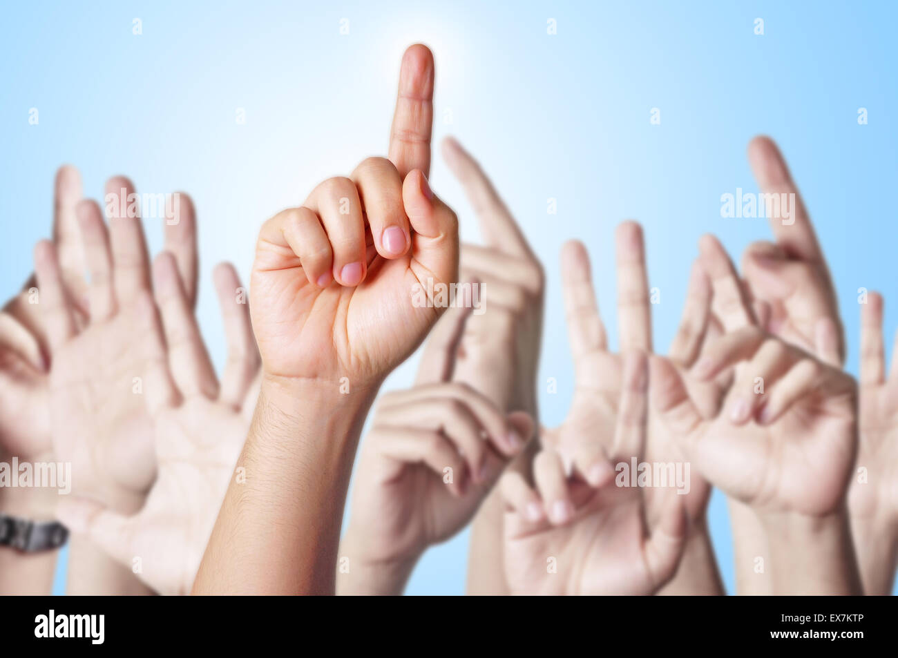 Group of people raising hands to answer a question - Stock Image