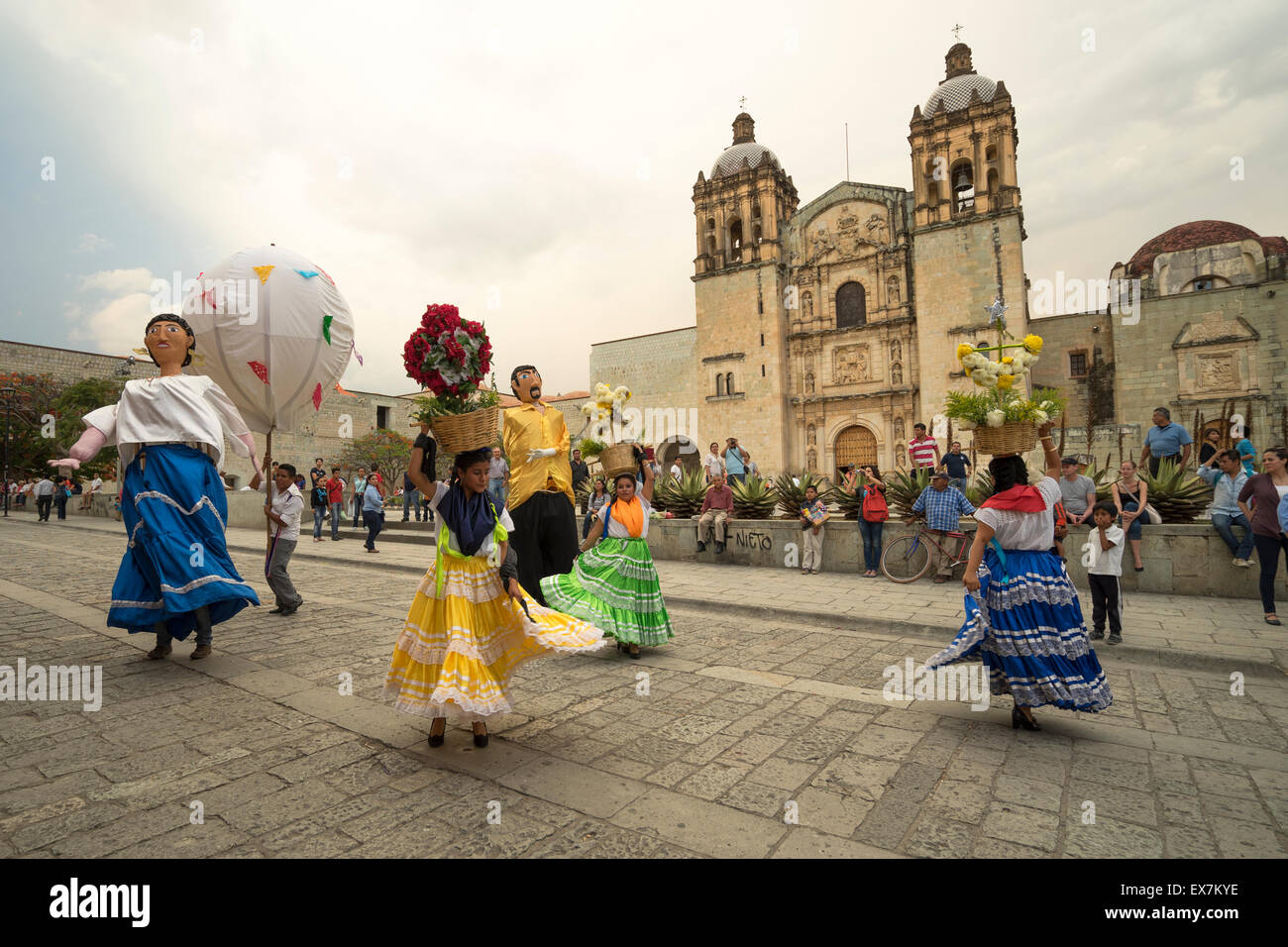 Women in costume and large figures dancing in front of Santo Domingo Church at a traditional festival in Oaxaca - Stock Image