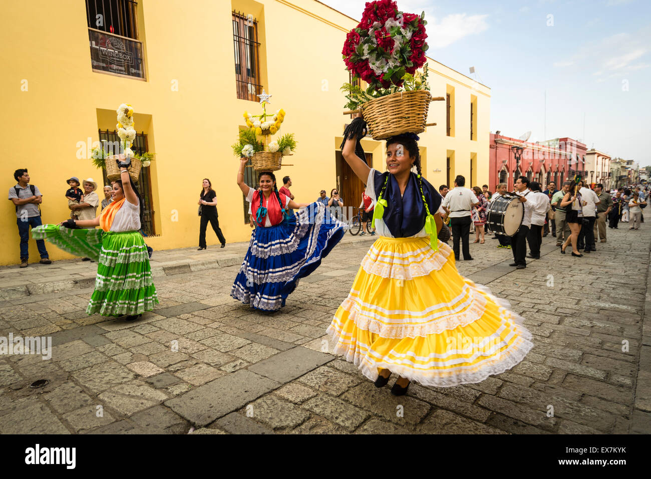 Women in traditional costume dancing and carrying flower baskets on their heads leading a parade at a festival in - Stock Image