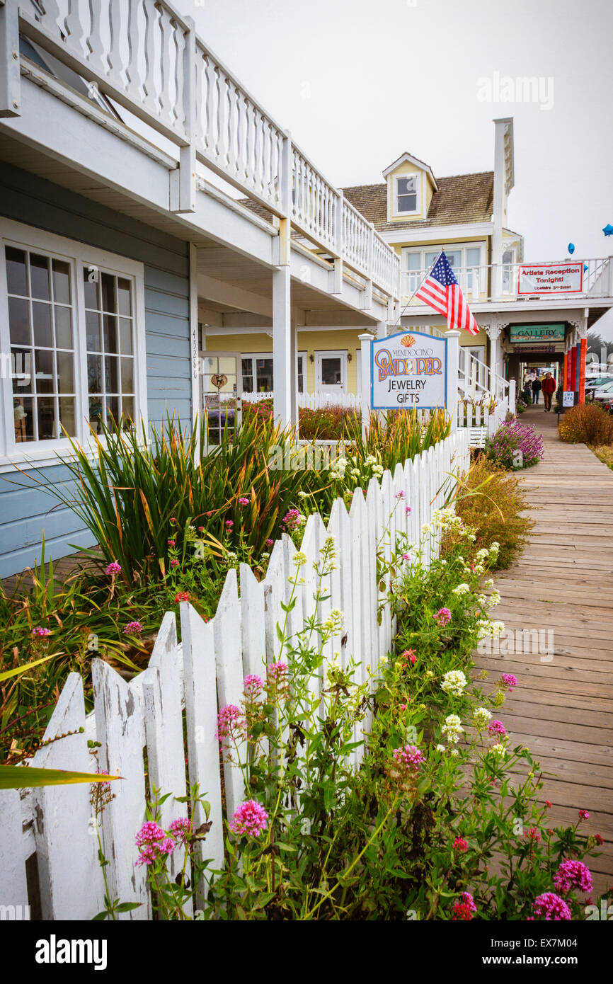 Galleries and craft stores with white picket fence on picturesque main street in downtown Mendocino, California - Stock Image