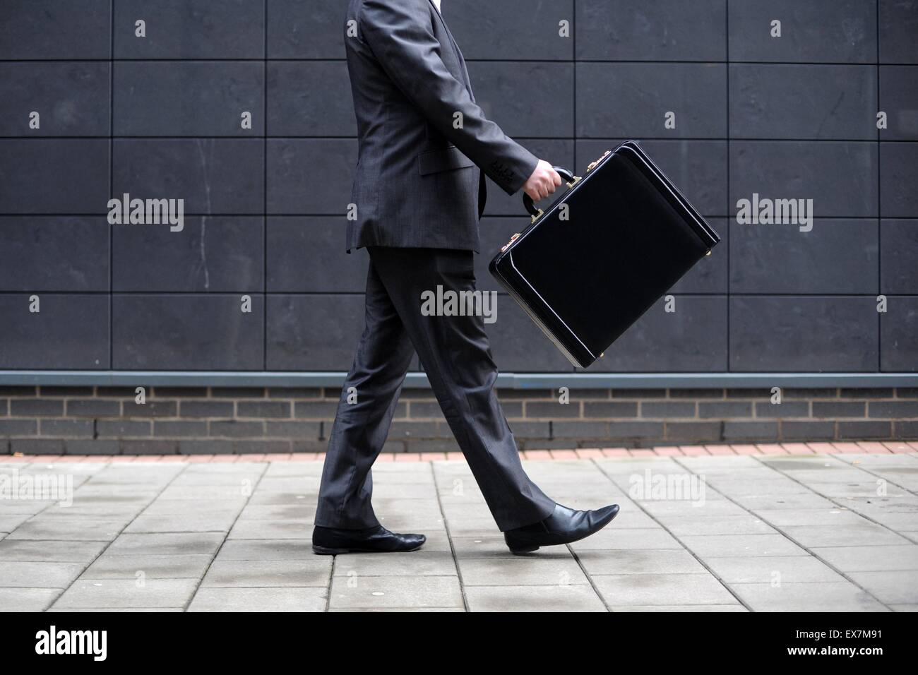 A business man carries a briefcase on the way to work at an office. - Stock Image
