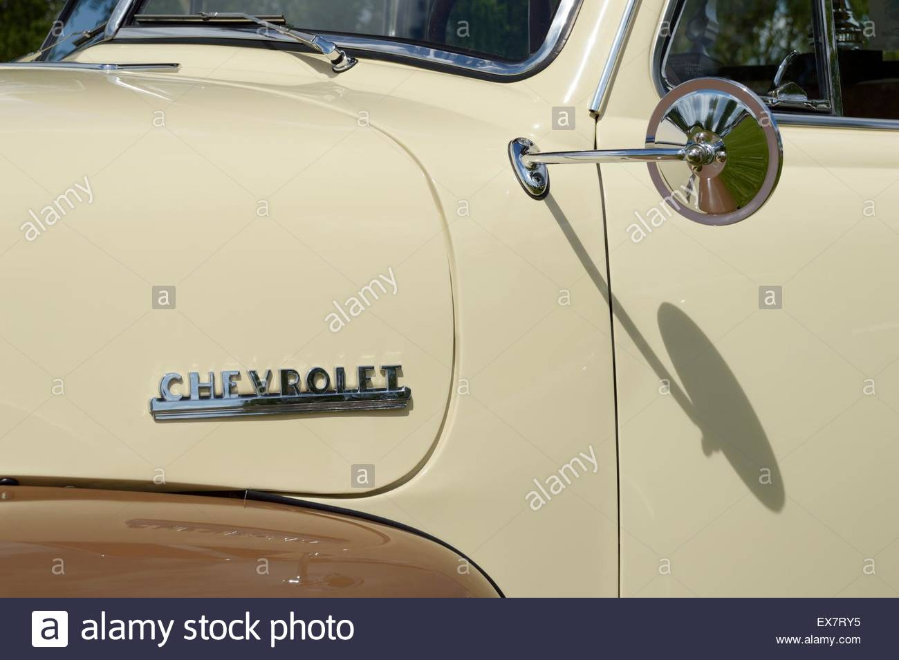 Side of an 1950's, two tone, Chevrolet truck and the shadow of the fender mirror on the drivers door - Stock Image