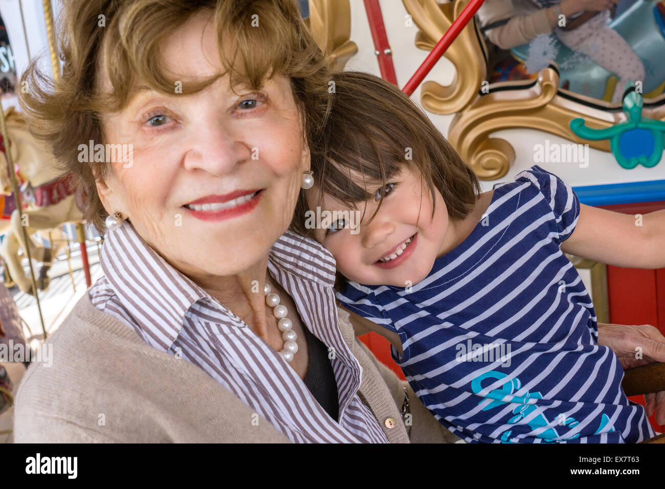 Toddler girl with her great-grandmother at the merry-go-round, San Diego, California - Stock Image