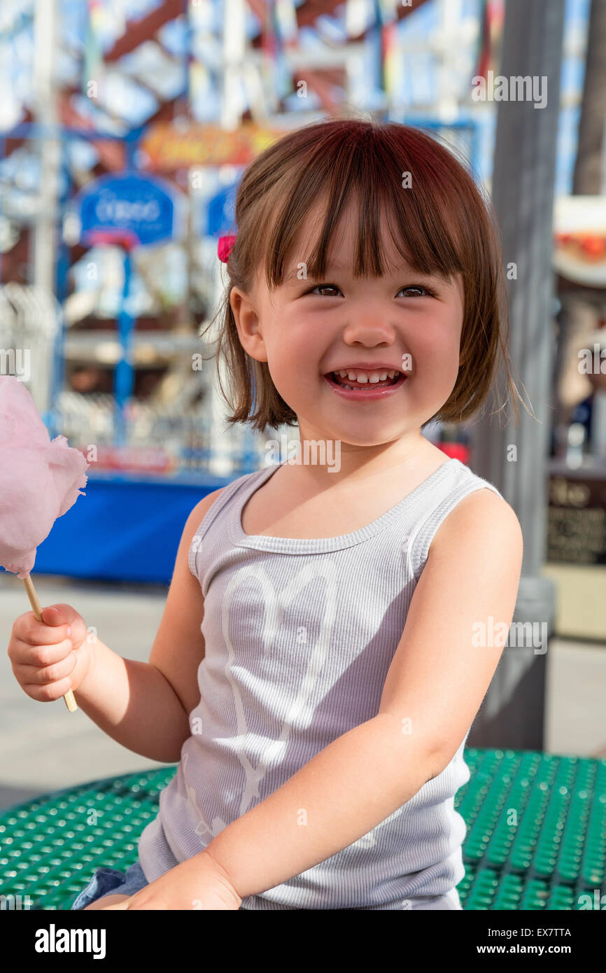 Three year old girl eating cotton candy at the amusement park, San Diego, California - Stock Image