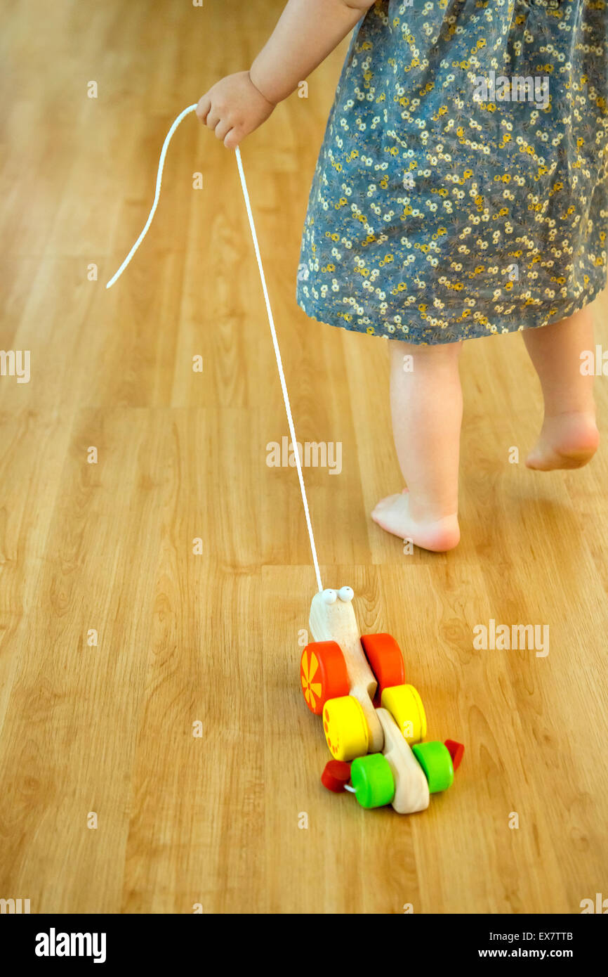 Baby girl pulling a wooden toy - Stock Image