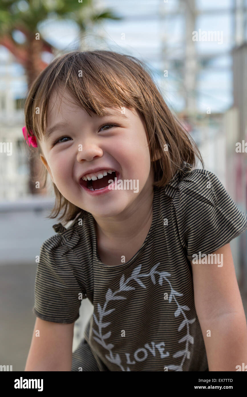 Amused three year old girl at the amusement park in San Diego, California - Stock Image