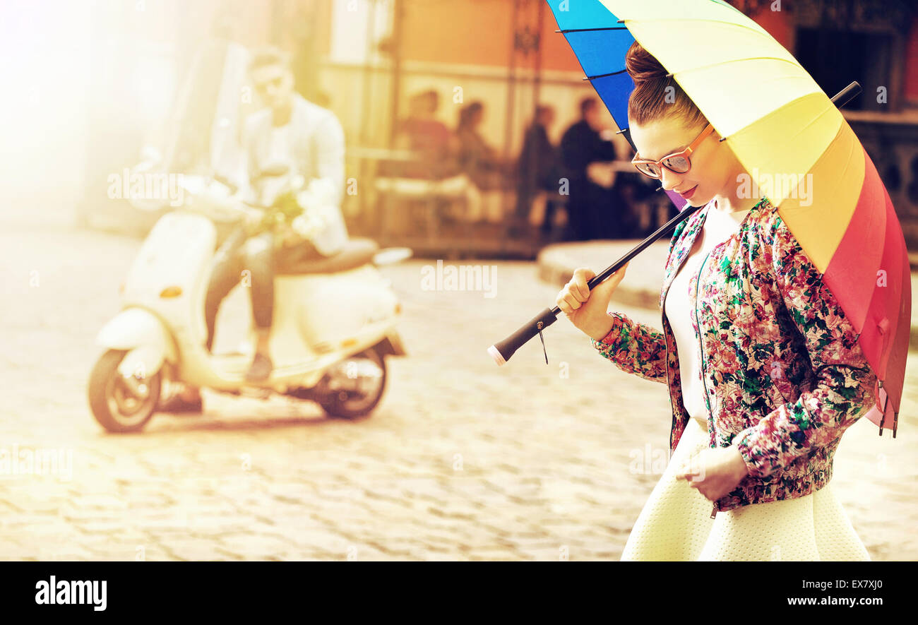 Portrait of a young woman holding a colorful umbrella - Stock Image