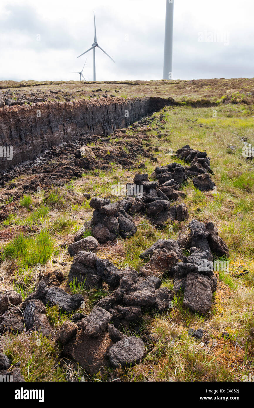 Wind turbines contrasting with peat cutting for fuel on the Isle of Lewis near Stornoway, Outer Hebrides, Scotland, - Stock Image