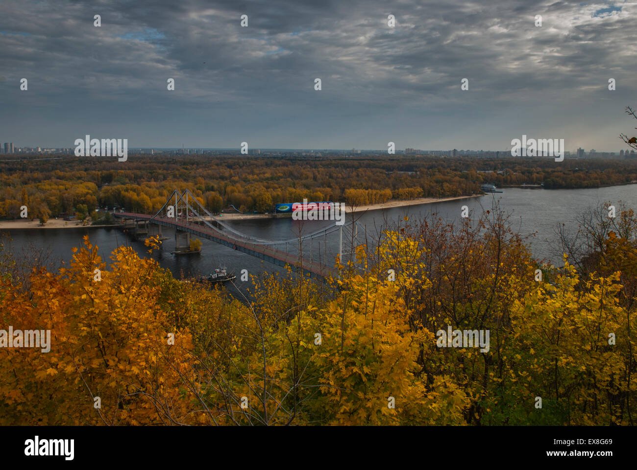 Parkovy Pedestrian Bridge crossing the river Dniper during Autumn in Kiev - Stock Image