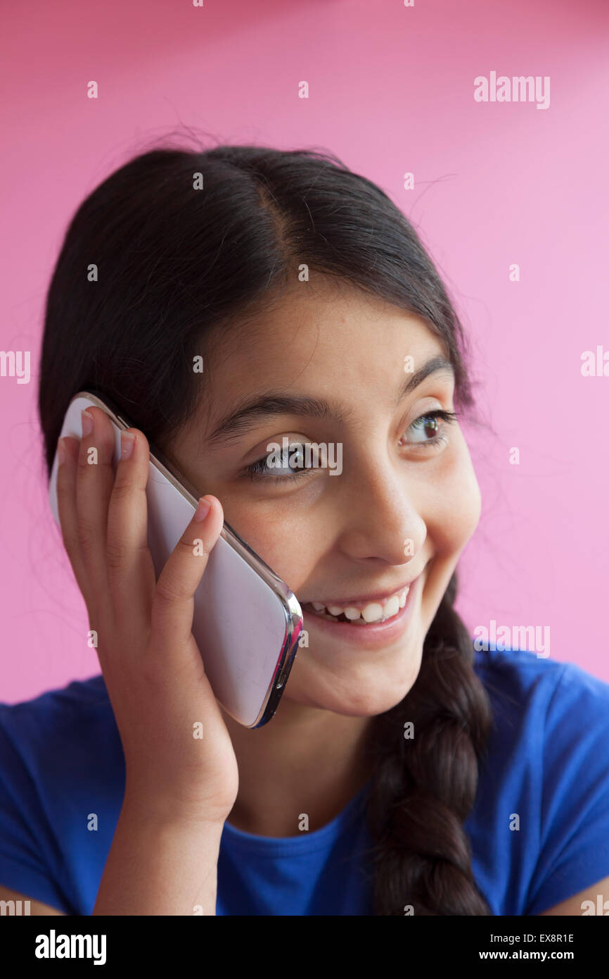 Happy teenage girl with her mobile phone - Stock Image