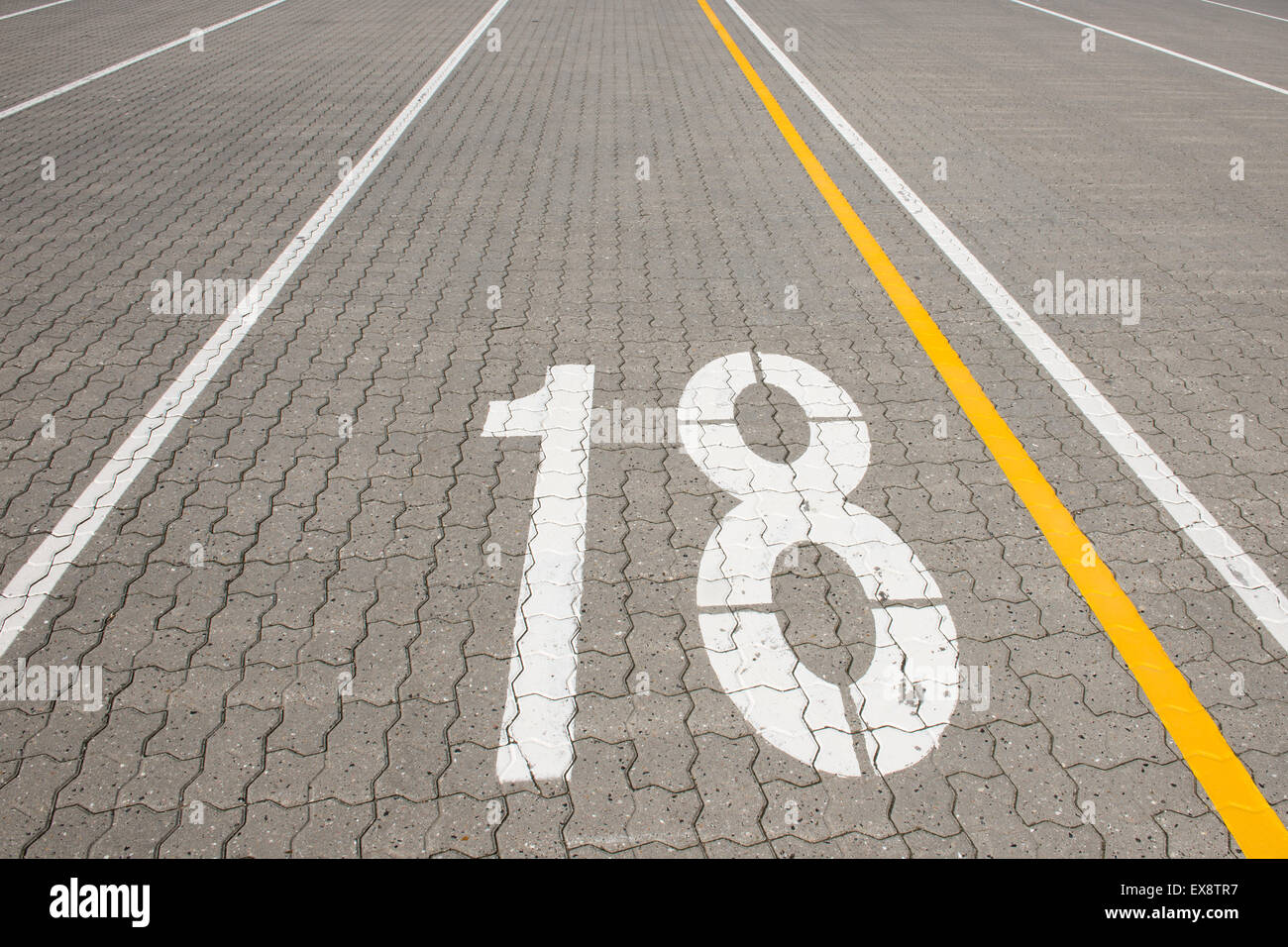 Ferry lane number 18 painted white on paving stone Stock Photo