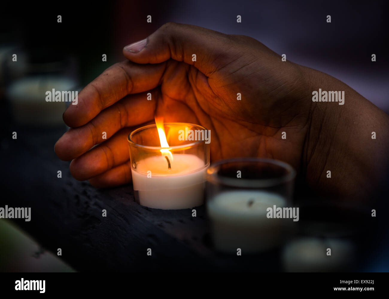 The Hand Of Marlande Lazard, From Miami, Keeps A Candle From Going Out That  Was Lit In Remembrance Of The Nine Live Lost At Eman