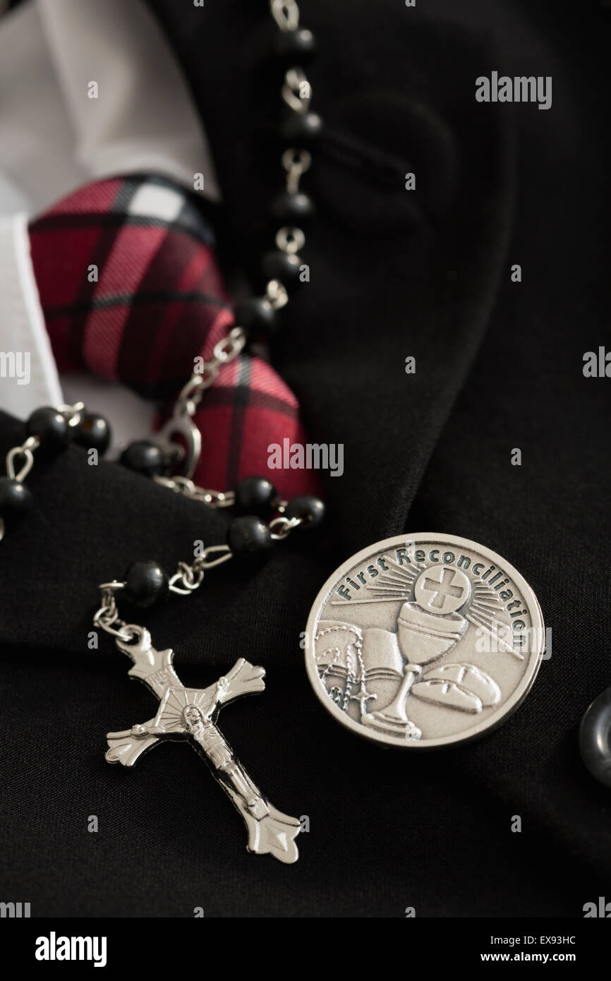 Rosary bead, silver badge with Christian symbols, formal clothes - Stock Image
