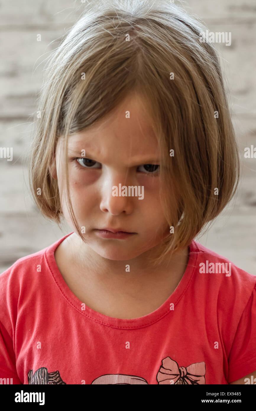 Very angry little girl in front of white wooden background - Stock Image