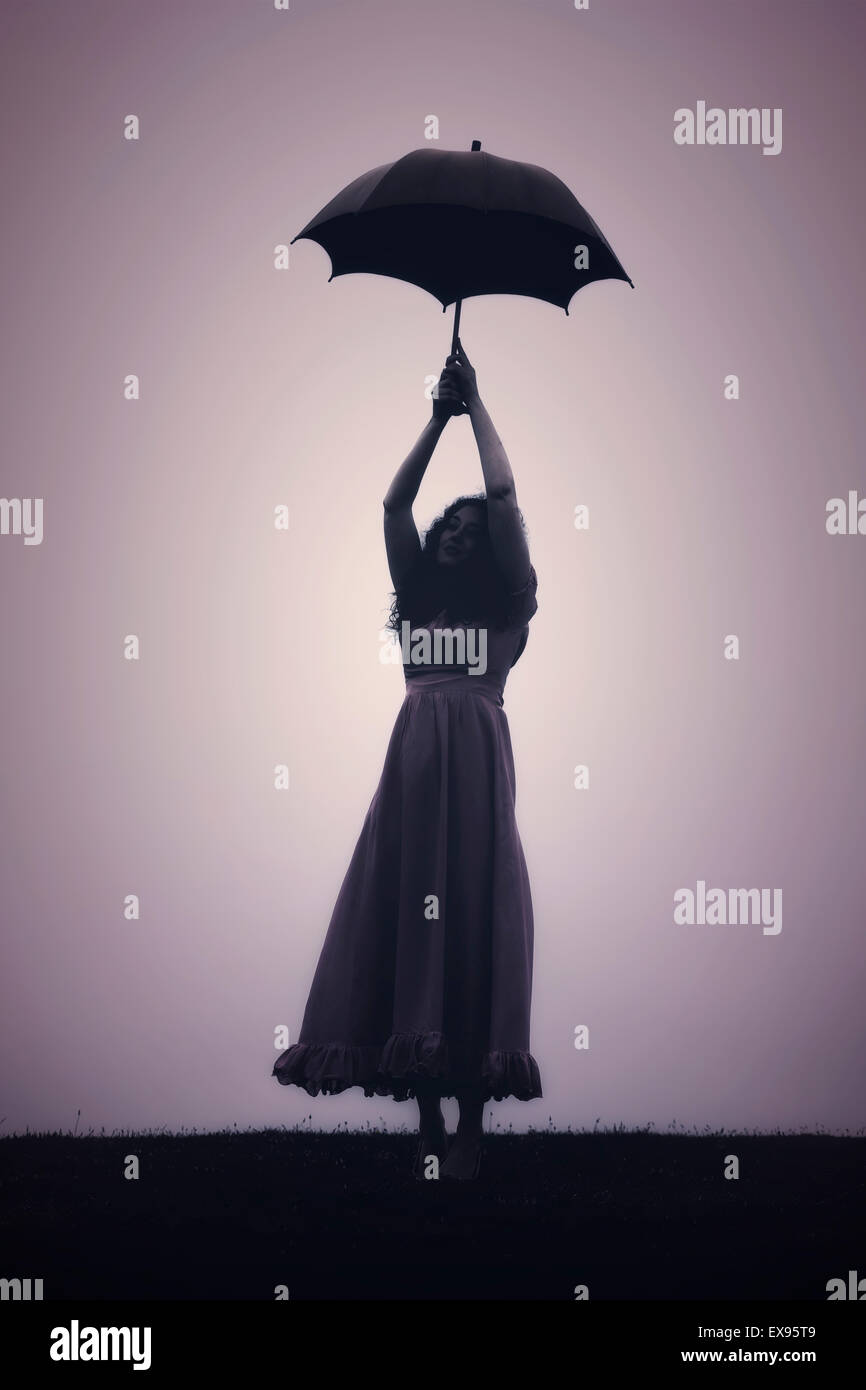 silhouette of a woman with an umbrella - Stock Image