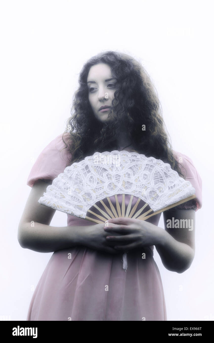 a beautiful woman with long curly hair in a pink dress with a white fan - Stock Image