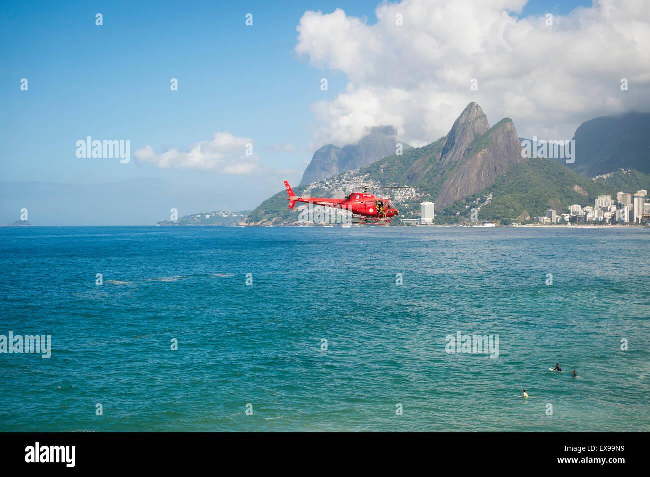 RIO DE JANEIRO - MARCH 22, 2015: Red Brazilian lifeguard bombeiros helicopter patrols the beaches. - Stock Image
