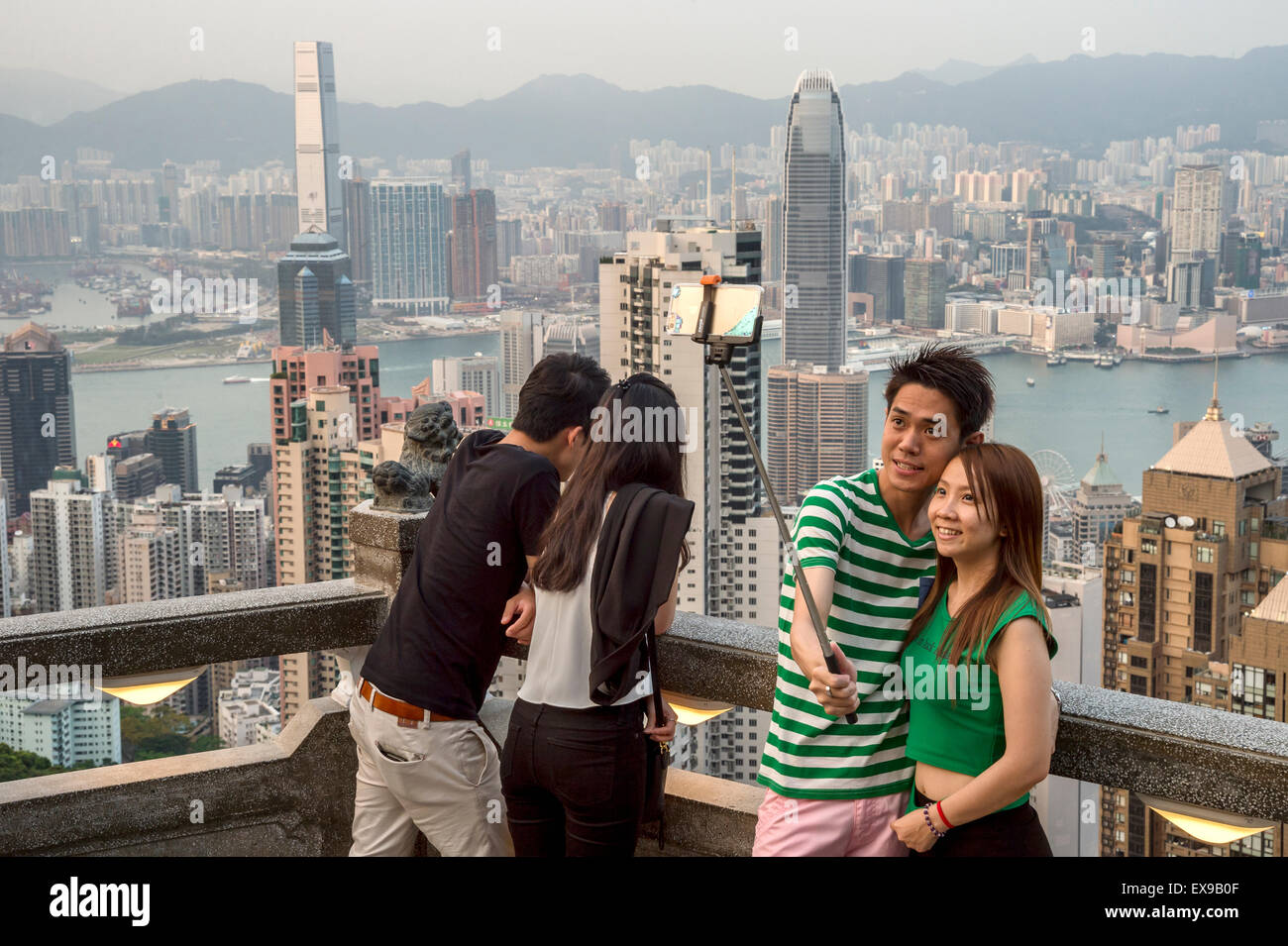 Young asian couple using a selfie stick in front of Hong Kong Skyline, from Victoria peak - Stock Image