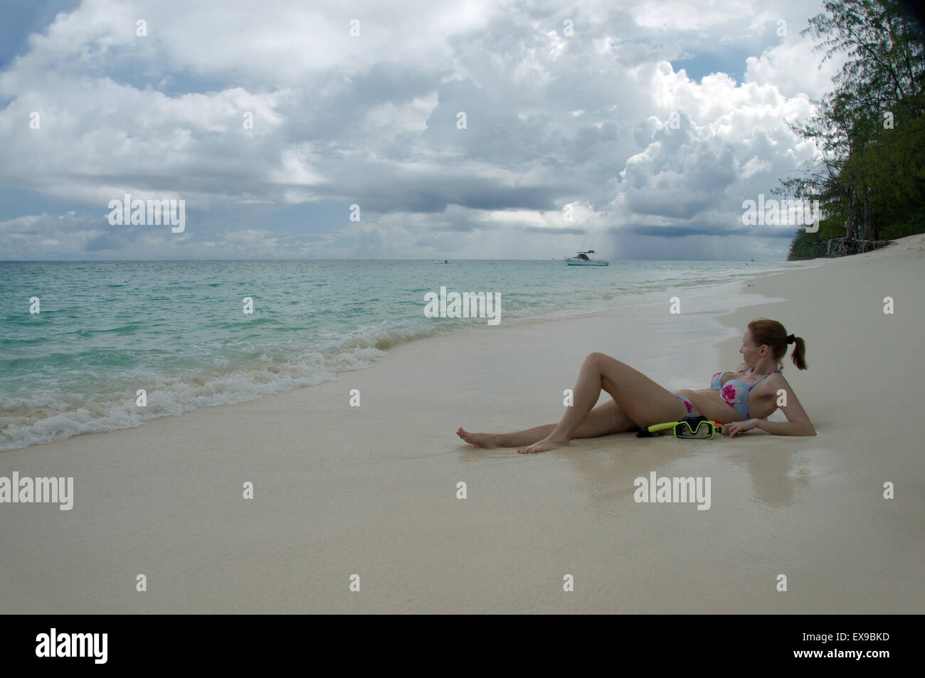 young woman lying on the sandy shores of the Indian Ocean, Denis island, Seychelles Stock Photo
