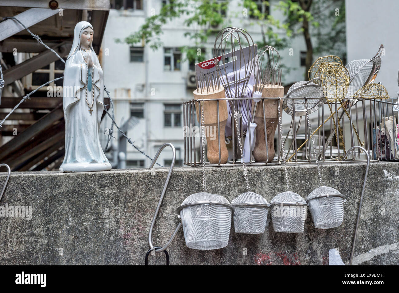 Virgin mary statuette next to kitchen utensils, in a Hong Kong street - Stock Image