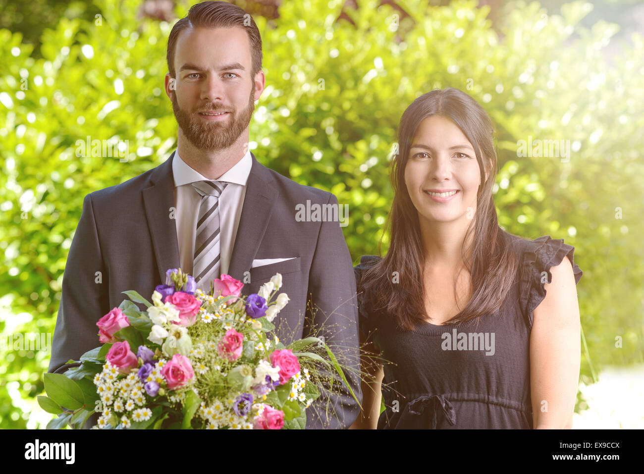 Happy Young Couple at the Garden with Bouquet of Assorted Fresh Flowers, Smiling at the Camera. - Stock Image