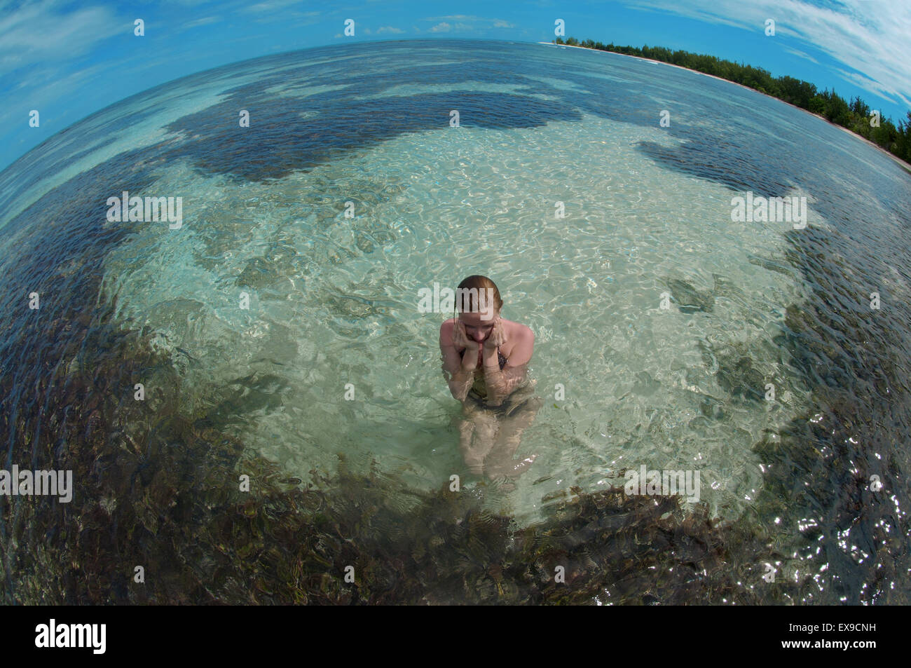 A young woman sits in water, Denis island, Indian Ocean, Seychelles Stock Photo