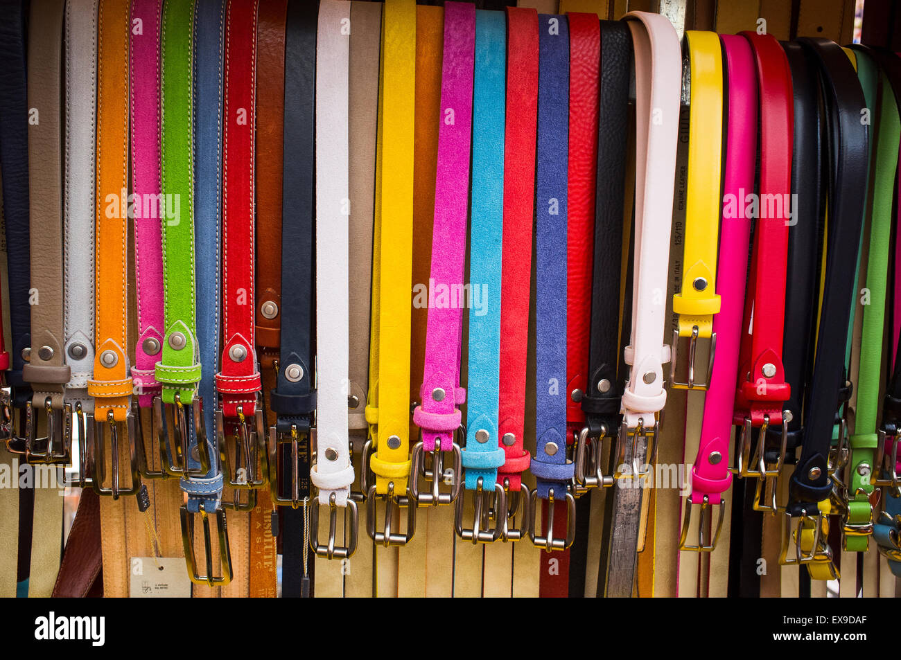 Colourful leather belts hanging up outside a shop in Italy. - Stock Image