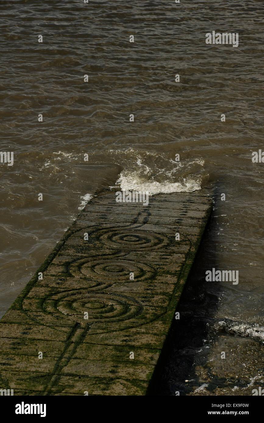 Stone slipway with runic symbols entering river - Stock Image