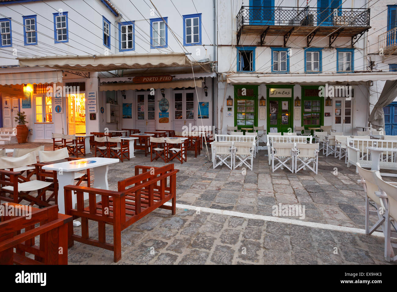 Terraces of coffee shops on the quay in the harbour of Hydra - Stock Image