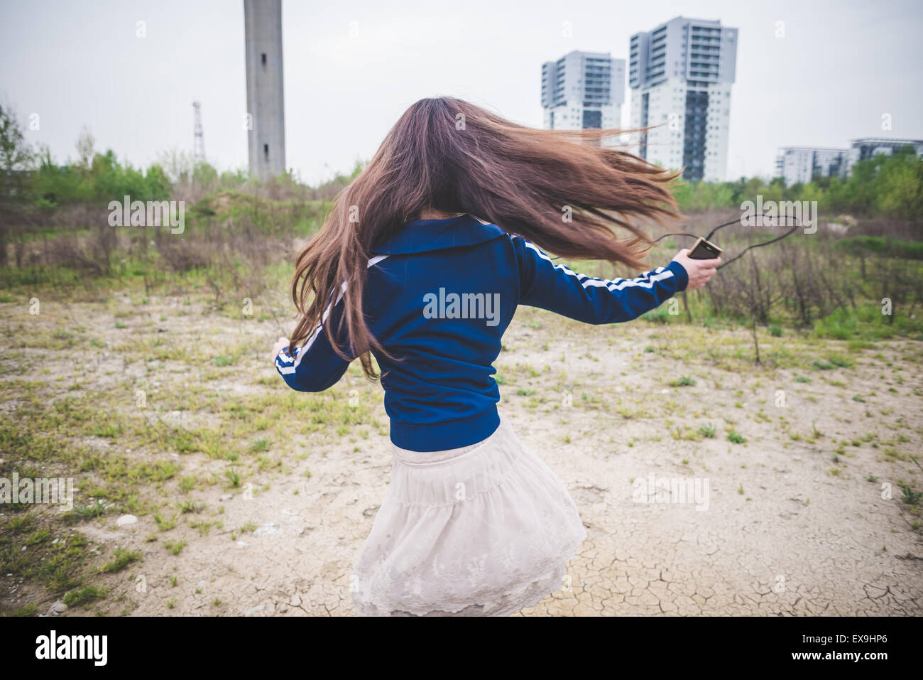 beautiful woman dancing in a desolate lurban landscape - Stock Image