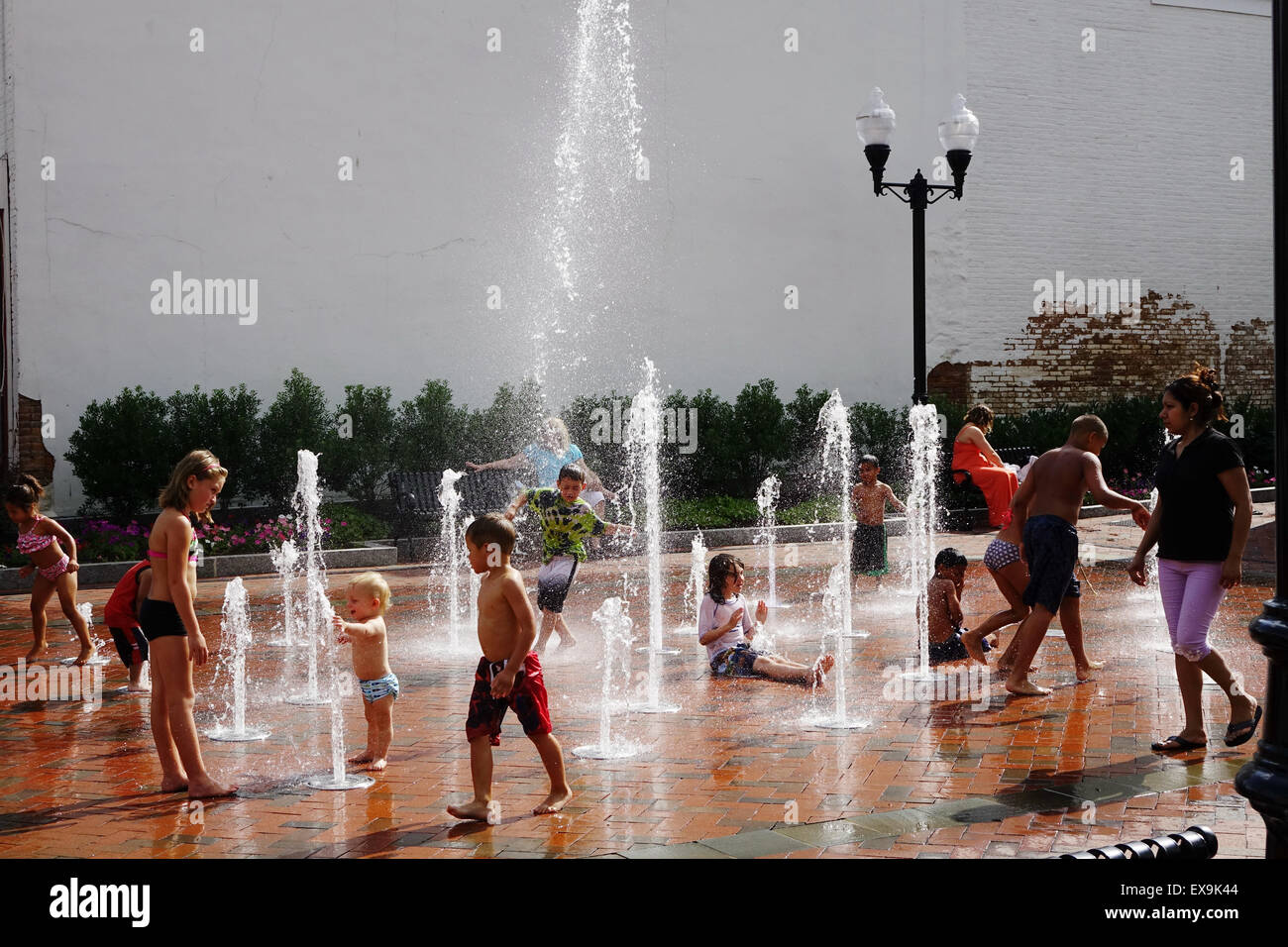 Children enjoying an outdoor fountain on a hot summer day in Old Town, Winchester, Virginia - Stock Image